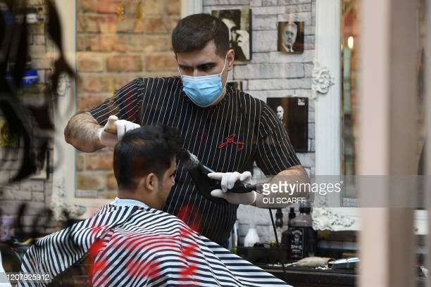 A barber wears a protective face mask as he cuts the hair of a customer in central Leeds northern England on the morning of March 21 a day after the...