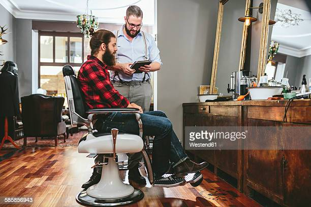 Barber with customer using digital tablet