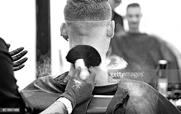 Barber working on a clients hair with brush