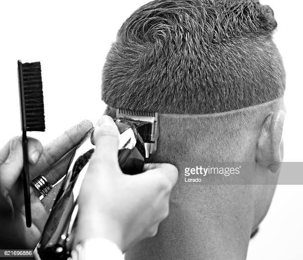 Barber working on a clients hair with clippers
