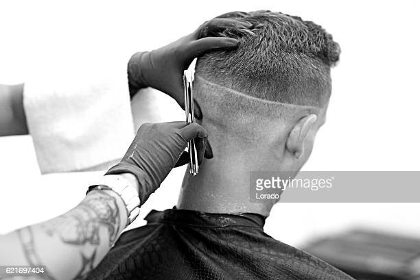 Barber working on a clients hair with cutthroat razor