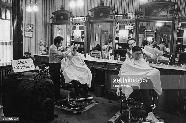 Barbers at work in a traditional barber's shop circa 1970
