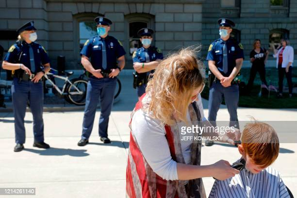 Barbers cut hair during the Michigan Conservative Coalition organized Operation Haircut outside the Michigan State Capitol in Lansing Michigan on May...