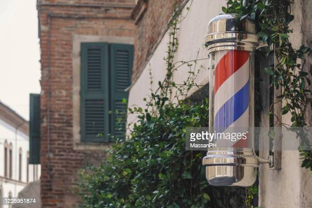 barber's pole on a street in ferrara, old style editing - barber pole stock pictures, royalty-free photos & images