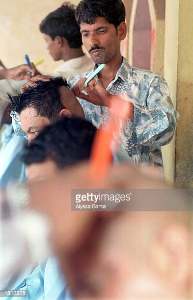 Barbers shave men''s heads June 3 2001 in the Nepalese capital of Kathmandu as a sign of respect for their king and other members of the royal damily...
