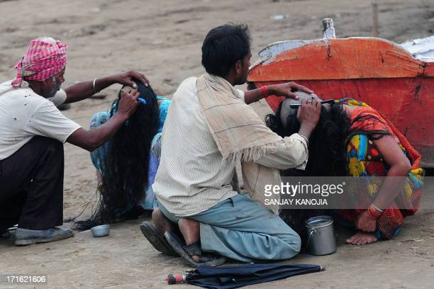 Barbers shave the heads of female devotees as part of a ritual where believers donate their hair at the Sangam in Allahabad on June 27 2013 Devotees...