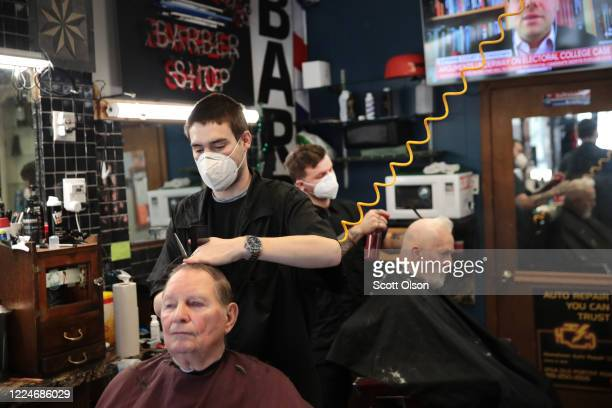 Barbers Steve Grimaldi and Chris Pouch cut hair for customers at Grimaldi's Barber Shop on May 13, 2020 in Chesterton, Indiana. Recently, Indiana...