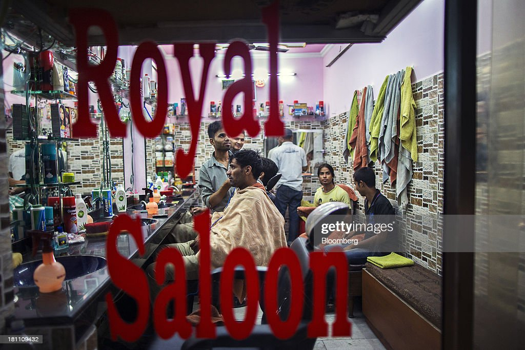 Barbers tend to customers at a shop in the old Delhi area of New Delhi, India, on Wednesday, Sept. 18, 2013. The Federal Reserves decision to postpone its rollback of U.S. stimulus offered Asian policy makers extra time to address domestic economic fragilities as the region copes with diminished capital inflows. Photographer: Prashanth Vishwanathan/Bloomberg via Getty Images