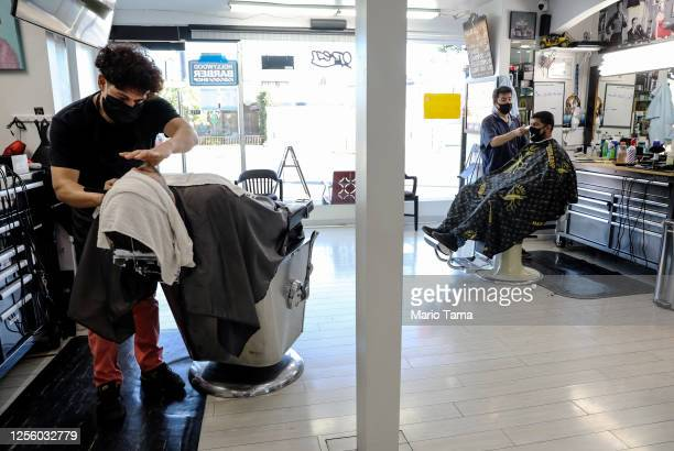 Barbers wear face masks as they work in the Hollywood Barber Shop shortly before closing amid new restrictions due to the COVID-19 pandemic on July...