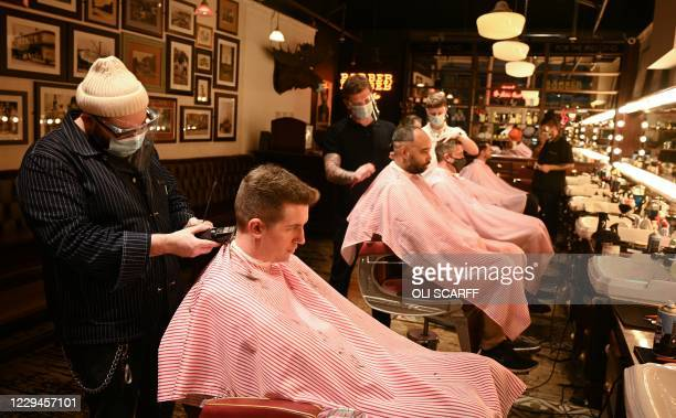 Barbers wearing a face masks or coverings due to the COVID-19 pandemic, cut customers' hair inside a barber's shop in central Manchester, north west...