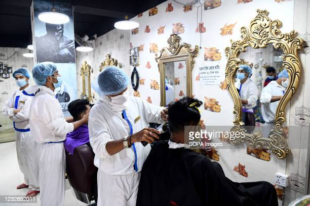 Barbers wearing personal protective equipment as a preventive measure against the spread of COVID19 attend to their salon clients in Dhaka.