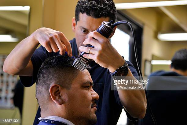 Barbershop owner Greg Salinas who is MexicanAmerican cuts the hair of Pascua Yaqui tribesman Jose Montana Friday March 21 2014 on the Pascua Yaqui...
