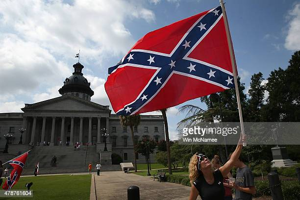 Barbie Byrd, of Columbia, South Carolina joins a group of demonstrators on the grounds of the South Carolina State House calling for the Confederate...