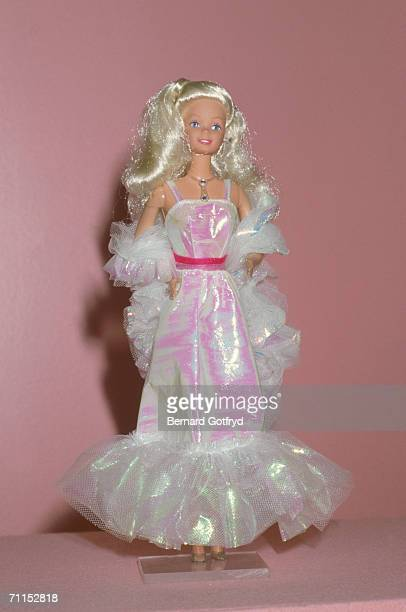 A barbie doll dressed in a shiny ball gown and stole on display 1980s