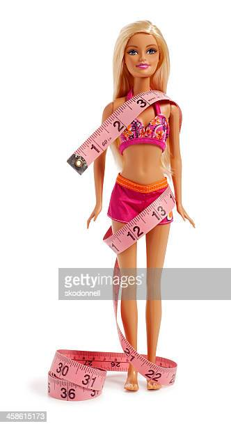barbie doll in a bikini wrapped with tape measure - barbie stock photos and pictures