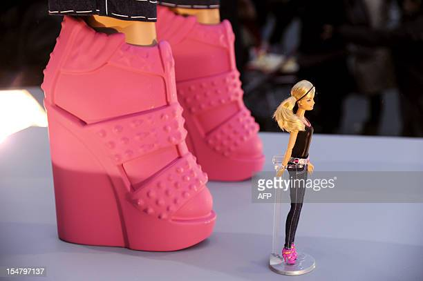 A Barbie doll is displayed in front of a fivemeter high replica of a Barbie doll at the entrance of the 'Kidexpo' show on October 26 at the Porte de...