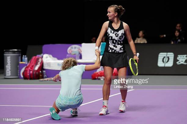 Barbora Krejcikova of the Czech Republic helps her partner and compatriot Katerina Siniakova up after a fall during their Women's Doubles match...