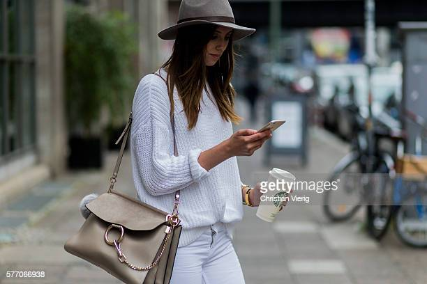 Barbora Ondrackova drinking a Starbucks coffee while on the phone wearing a grey Tophop hat a white American Apparel sweater white Zara ripped jeans...