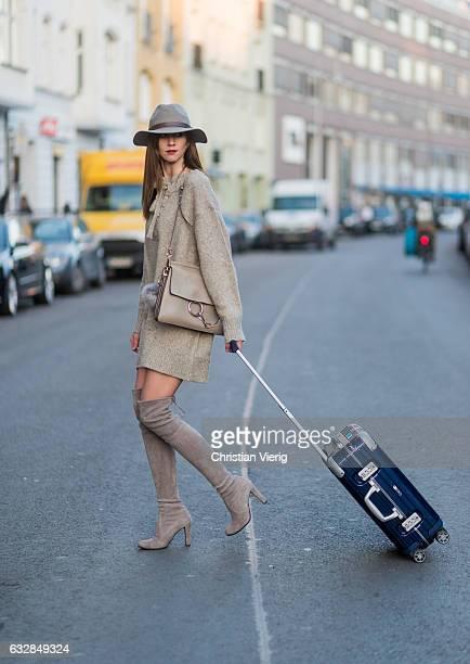 Barbora Ondrackova with a navy Rimowa suitcase wearing a beige oversized knit Zara beige Stuart Weitzman overknees a beige Chloe bag a grey HM hat on...