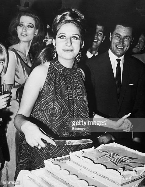 """Barbra Streisand cuts the cake a farewell party for her given by the cast of """"Funny Girl"""" in London. Streisand was starring in the musical, and left..."""