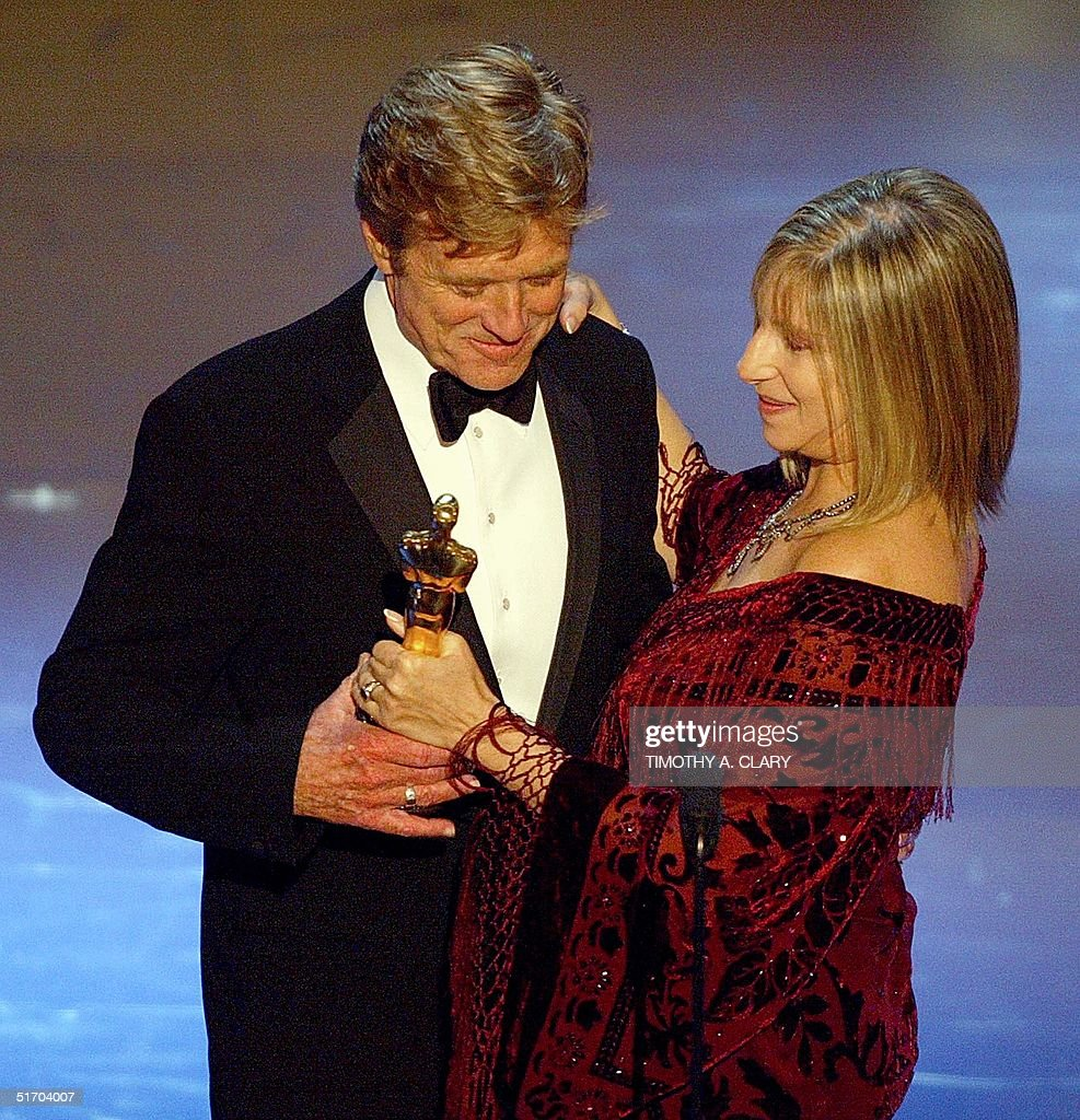 Barbra Streisand hands Robert Redford's his Oscar for his four decades of screenwork and his support to independent filmmaking, during the 74th Academy Awards at the Kodak Theater in Hollywood 24 March 2002.
