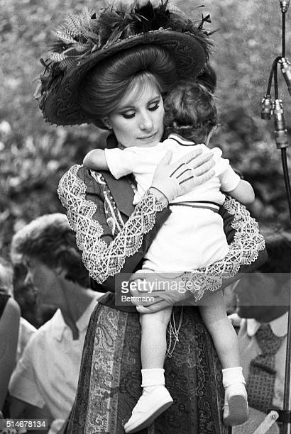 Barbra Streisand in costume comforts her son on the set of Hello Dolly