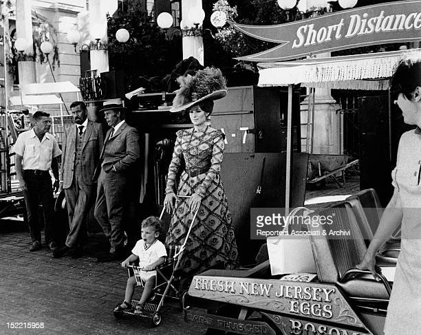 Barbra Streisand who plays the role of Dolly Levi in the movie Hello Dolly wheels her son Jason Gould's baby buggy on the set of the film USA 1968