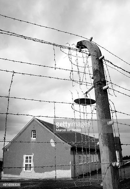 CONTENT] Barbwire fence and old barracks at the German concentration camp Buchenwald
