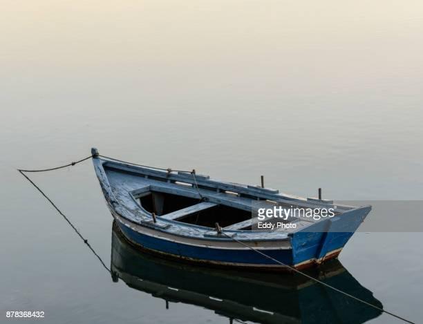 Barca aislada en medio de la ria con reflejo en una mañana tranquila