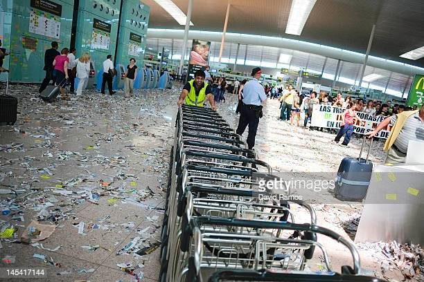 Barcelona Airport staff push trolleis among rubbish and papers as Barcelona Airport cleaning staff protest against budget cuts at the El Prat...