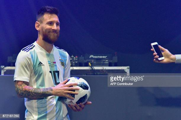 Barcelona and Argentina forward Lionel Messi poses with the official match ball for the 2018 World Cup football tournament named 'Telstar 18' during...