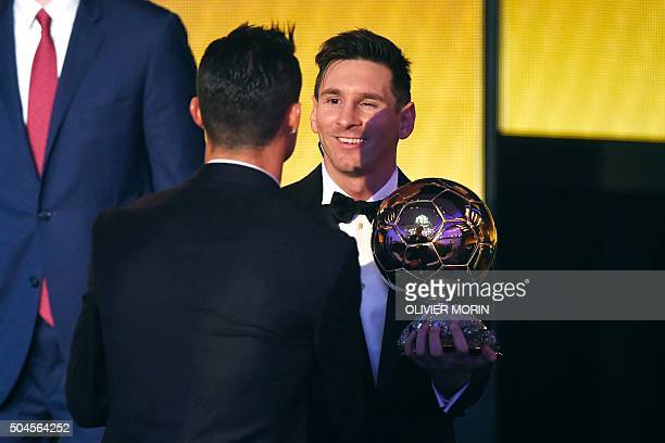 FC Barcelona and Argentina's forward Lionel Messi holds his trophy as he shakes hands with Real Madrid and Portugal's forward Cristiano Ronaldo after...