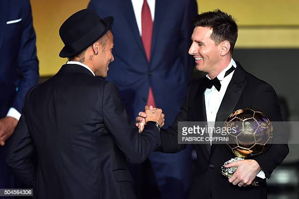 Barcelona and Argentina's forward Lionel Messi holds his trophy as he shakes hands with FC Barcelona and Brazils forward Neymar after receiving the...