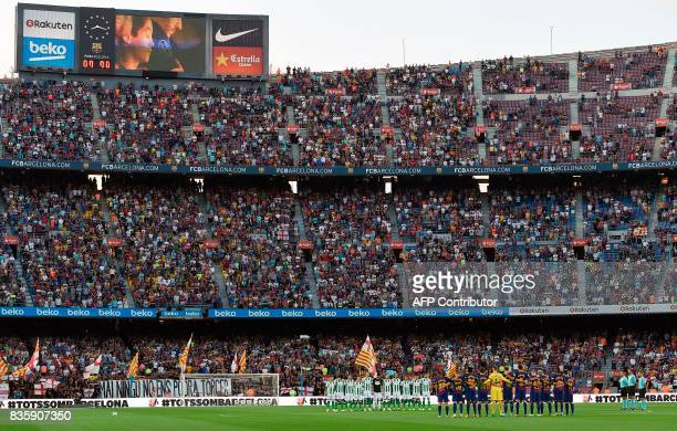 Barcelona and Betis's football players observe a minute of silence as they wear jerseys reading 'Barcelona' instead of their names to pay tribute to...