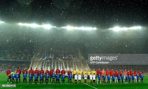 Barcelona and Olympiacos teams line up in the rain before the UEFA Champions League group D football match FC Barcelona vs Olympiacos FC at the Camp...