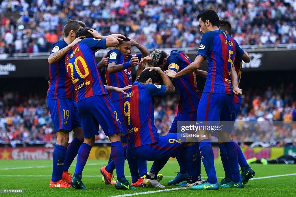 FC Barcelona are hit by objects thrown from the seats after Lionel Messi of FC Barcelona scores his team's third goal from the penalty spot during the La Liga match between Valencia CF and FC Barcelona at Mestalla stadium on October 22, 2016 in Valencia, Spain.