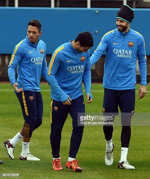 FC Barcelona defender Gerard Pique speaks with forward Luis Suarez beside defender Adriano during their training session at the Club World Cup...