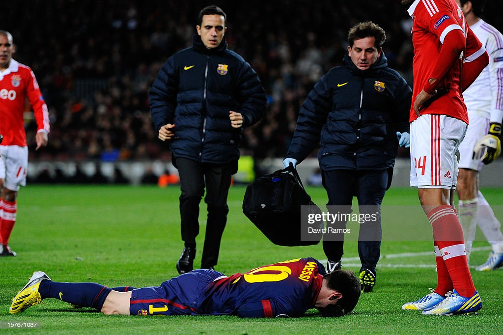 FC Barcelona doctors run towards Lionel Messi of FC Barcelona as he reacts on the pitch after being injured during the UEFA Champions League Group G match between FC Barcelona and SL Benfica at Nou Camp on December 5, 2012 in Barcelona, Spain.