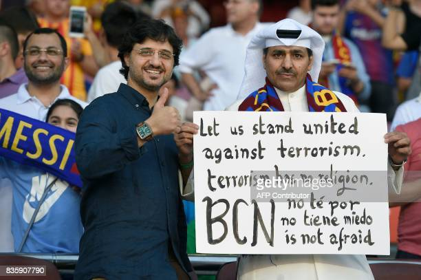 Barcelona fan hold a placard with slogans against terrorism before the Spanish league footbal match FC Barcelona vs Real Betis at the Camp Nou...