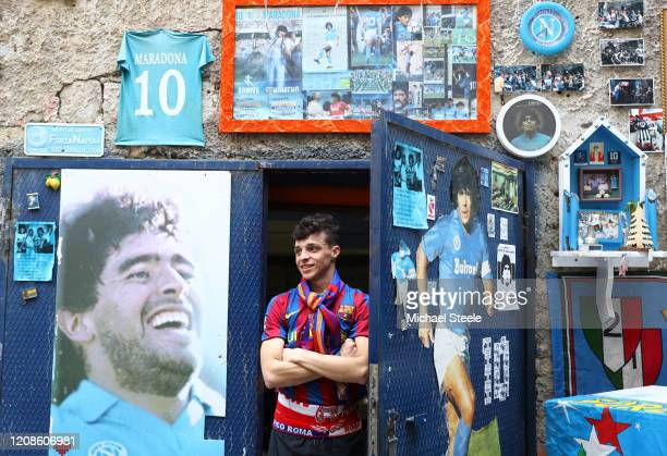 Barcelona fan stands amongst street art showing ex Napoli player Diego Maradona in the city of Naples ahead of the UEFA Champions League round of 16...