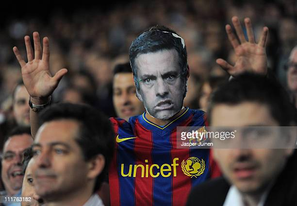 Barcelona fan with a cardboard mask of Real Madrid head coach Jose Mourinho follows the UEFA Champions League quarter final first leg match between...