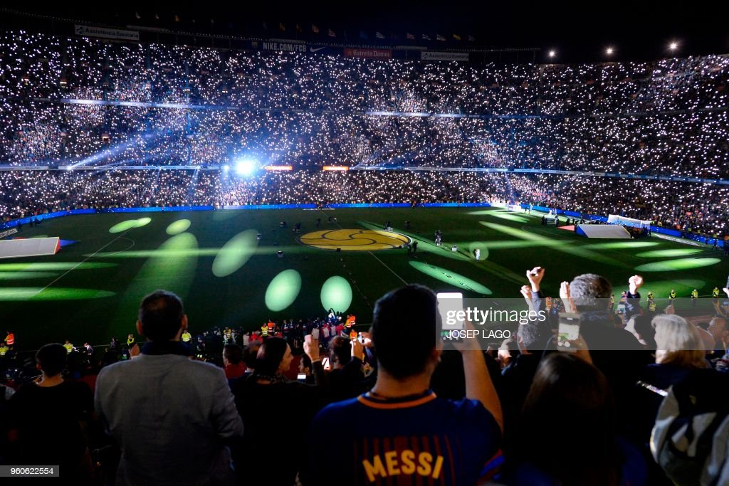 TOPSHOT - Barcelona fans attend a tribute for Barcelona's Spanish midfielder Andres Iniesta at the end of the Spanish league football match between FC Barcelona and Real Sociedad at the Camp Nou stadium in Barcelona on May 20, 2018. - Iniesta, who joined Barcelona's academy 22 years ago, played his final game for the club.