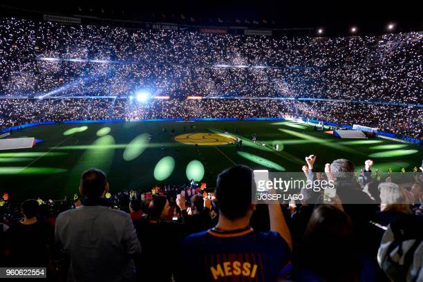 TOPSHOT Barcelona fans attend a tribute for Barcelona's Spanish midfielder Andres Iniesta at the end of the Spanish league football match between FC...