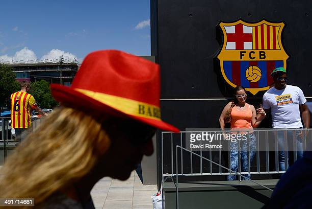 Barcelona fans pose for a picture beneath a FC Barcelona emblem prior to the La Liga match between FC Barcelona and Club Atletico de Madrid at Camp...