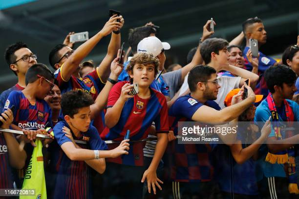 Barcelona fans take photos prior to the game between SSC Napoli and FC Barcelona during a preseason friendly match at Hard Rock Stadium on August 07...