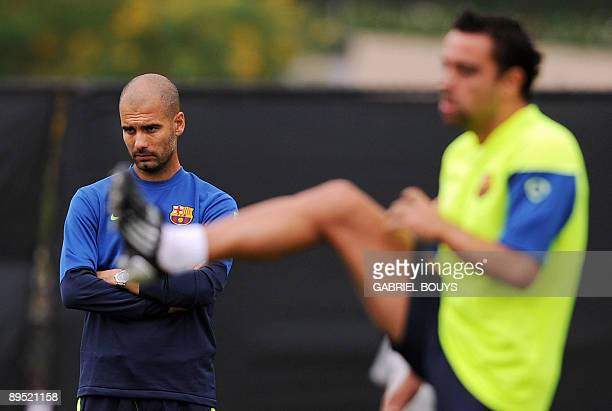 Barcelona FC head coach Josep Guardiola looks on as midfielder Xavi Hernandez streches during a training session at UCLA in Los Angeles on July 30,...