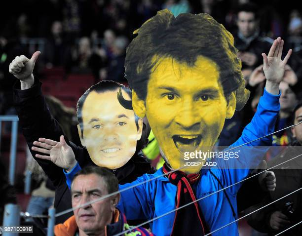 A Barcelona FC's fan with a giant mask of Barcelona's Argentinian forward Lionel Messi made with cardboard flanked by a masked fan of Barcelona's...