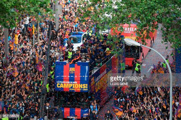 Barcelona football club players and staff parade aboard an opentop bus to celebrate their 25th La Liga title in Barcelona on April 30 2018 Barcelona...