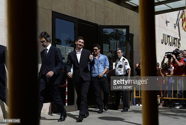 Barcelona football star Lionel Messi gives the thumbs up as he leaves the courhouse in the coastal town of Gava near Barcelona on September 27 2013...