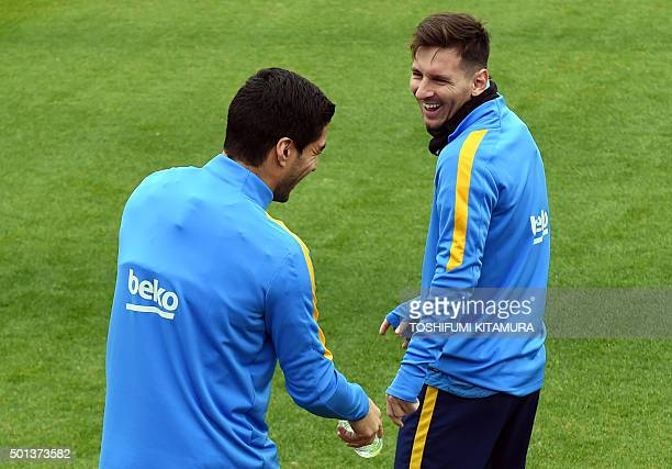 FC Barcelona forward Lionel Messi interacts with forward Luis Suarez while entering the pitch during their training session at the Club World Cup...